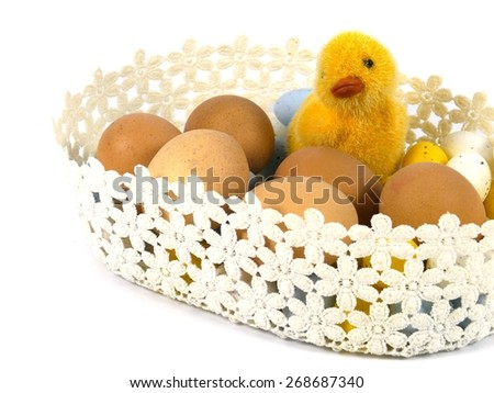 A yellow chicken in a basket with boiled chicken eggs as a Easter table decoration over white - stock photo