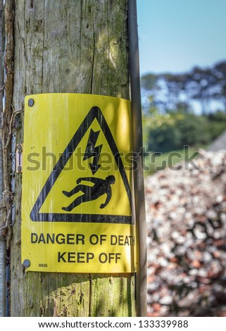 "A yellow ""Danger of Death"" ""Keep Off"" warning sign typical in the UK.  Nailed to an wooden utility pole in the countryside. - stock photo"