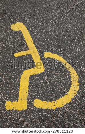 A yellow Disabled symbol painted in a Parking Bay. - stock photo