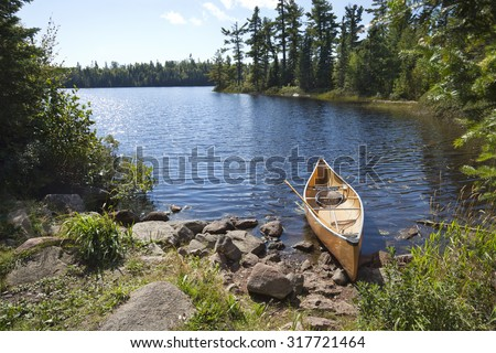 A yellow fisherman's canoe on a rocky shore of a northern Minnesota lake - stock photo