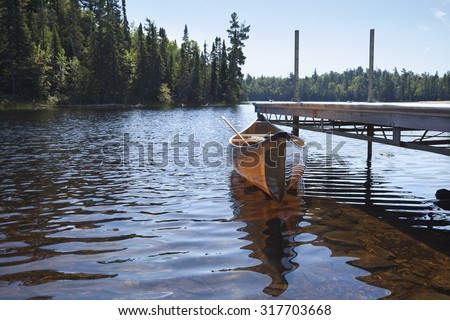 A yellow kevlar lightweight canoe tied to a dock on a trout lake in northern Minnesota - stock photo