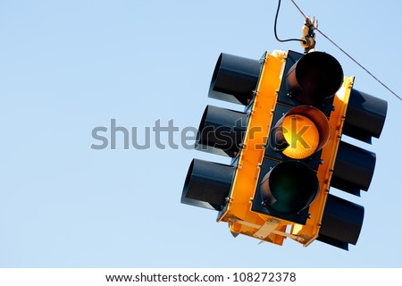 A yellow light traffic signal with blue sky copy space - stock photo