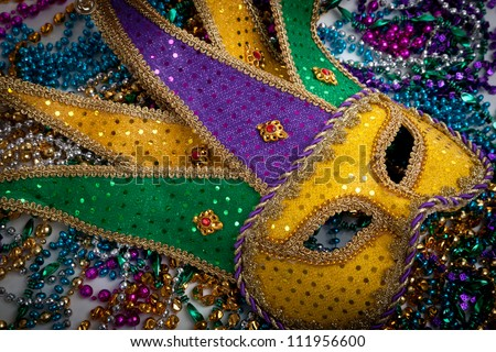 A yellow Mardi Gras jester mask and beads - stock photo