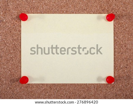 A yellow note page pinned to a noticeboard. - stock photo