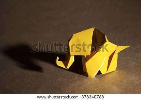 A yellow origami elephant isolated on craft paper background. - stock photo