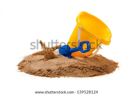 A yellow pail, blue shovel and a starfish on sand on a white background with copy space - stock photo