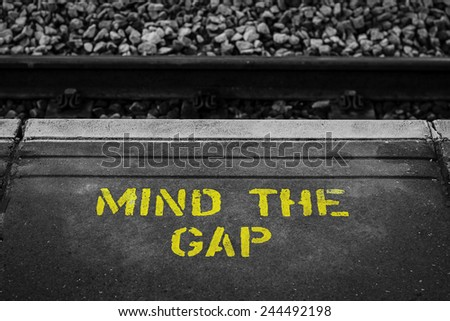 """A yellow painted warning sign """"Mind The Gap"""" at a British railway station - stock photo"""