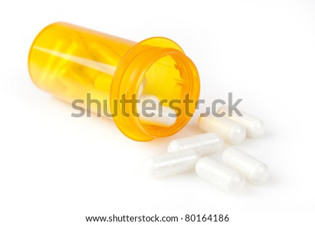 A yellow pill bottle against a white background - stock photo