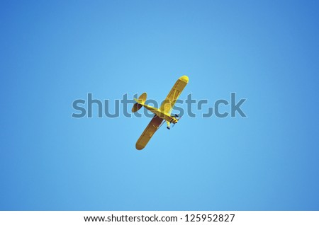 A yellow plane flying high in the blue sky.