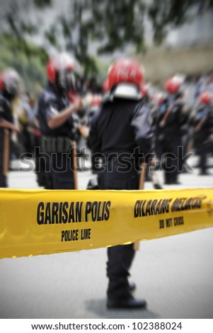 A yellow police line tape in dual language, Bahasa Indonesia and English, with riot police in the background.