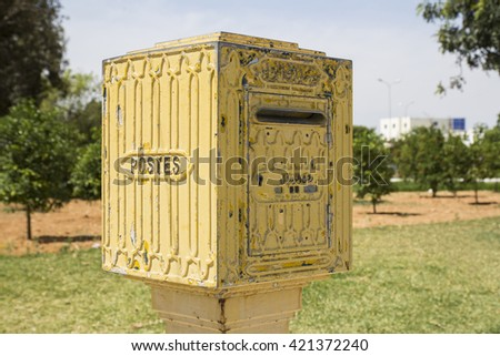 A yellow post box set against a de-focused city park background in Tunisia - stock photo
