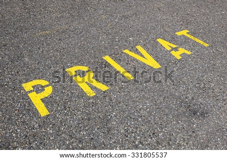 A yellow road marking is indicating that this is a private parking spot or entrance. It can also be used as a photo that describes modern times and difficulties we have on issues regarding privacy.