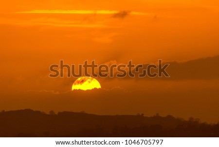 A yellow setting sun disappears behind clouds in an orange-coloured sky in Herefordshire, UK