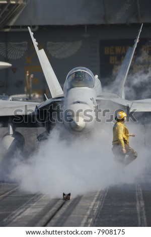 "A ""Yellow Shirt"" Aircraft Director in Front of an F/A-18F Super Hornet Aboard the Nuclear Aircraft Carrier, USS Enterprise - stock photo"