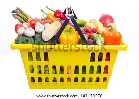 A yellow shopping basket full of fruits and vegetables isolated on white. - stock photo