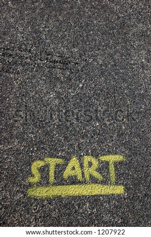 A yellow start painted on black pavement - stock photo