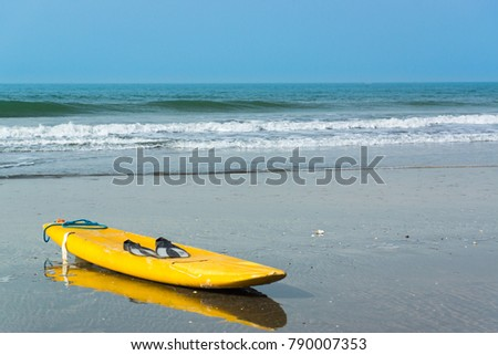 A yellow surfboard lays on Kotu Beach in The Gambia, West Africa