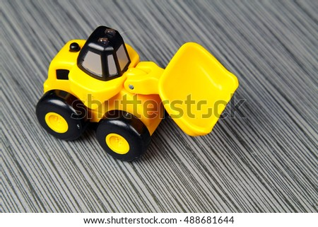 A yellow toy truck on a grey stone background with cpy space, selective focus