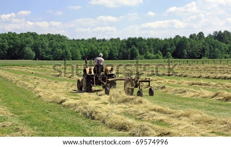 a yellow tractor turning hay in a field in summer under a blue sky - stock photo