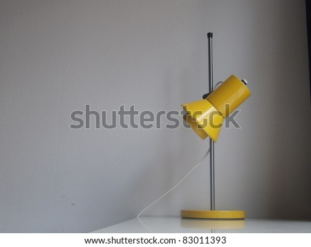 A yellow vintage lamp on a desk