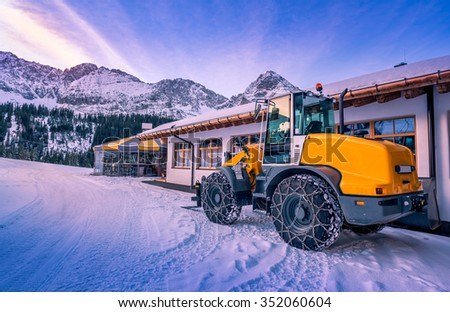 A yellow wheel loader with chains on its tires, ready to remove the snow from the mountain paths. A lovely winter scenery from the austrian Alps.  - stock photo