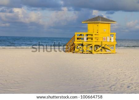 A yellow wooden lifeguard hut on an empty morning beach - stock photo