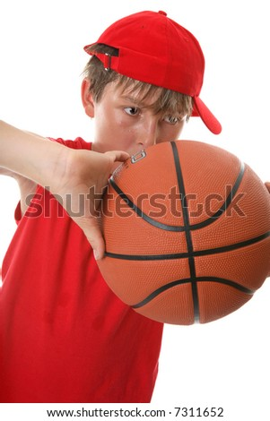 A young active boy playing with a basketball