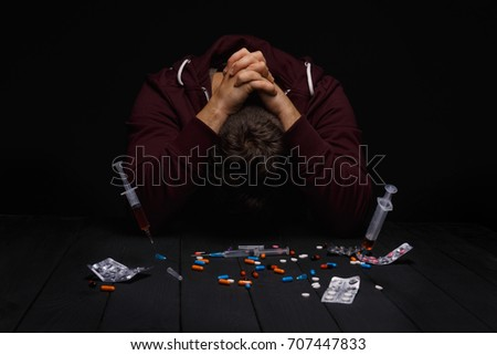 A young addict under the influence of narcotics sitting at the table on a saturated black background. A lot of pills, syringes, and drugs on a desk. An addict clings to his head with his own hands.