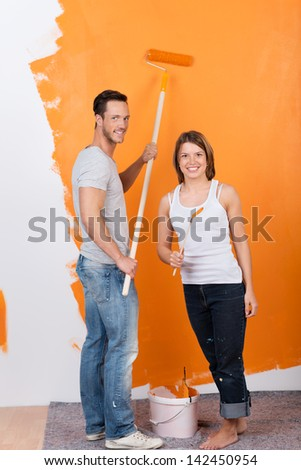 A young adult couple painting yellow wall of their new house - stock photo
