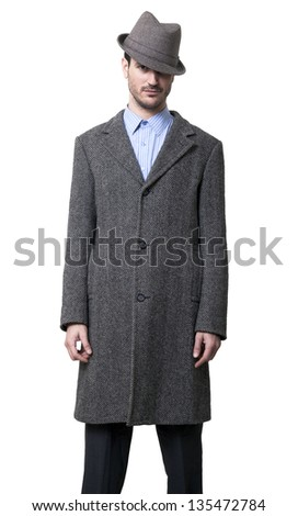 A young adult male wearing a gray overcoat and a gray hat that is covering his left eye, which adds to his charmant look in his other eye. Isolated on white background. - stock photo