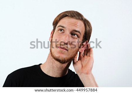 A Young Adult Male Wearing Dark T-Shirt with His Hand Near His Ear. Gestures Can Not Hear or Talk Louder.  - stock photo