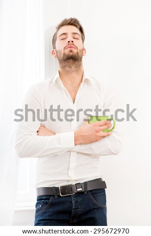 A young adult man at home drinking coffee.