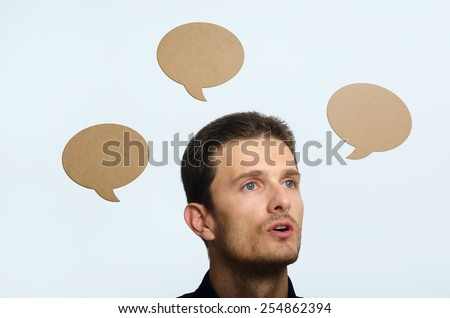 A young adult man speaking with text balloons - stock photo