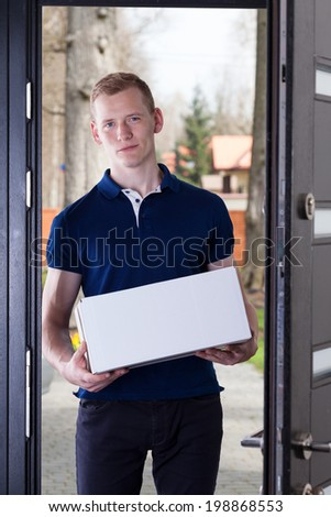 A young adult standing in at the door with a package