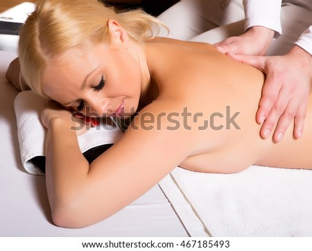 A young adult woman receiving a massage from a male masseur.
