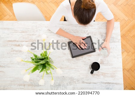 A young adult woman seen from above with tablet.  - stock photo