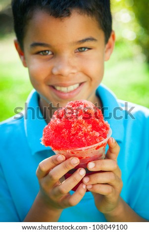 A young African-American boy holds a snow cone as he smiles at the camera. - stock photo