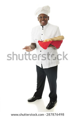A young African American chef offering the viewer to sample some of his specialty breads.  On a white background.