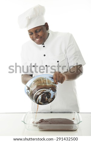 A young African American chef pouring chocolate batter from his mixing bowl to the backing dish.  On a white background. - stock photo