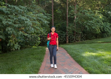 A young african american college student walking on campus