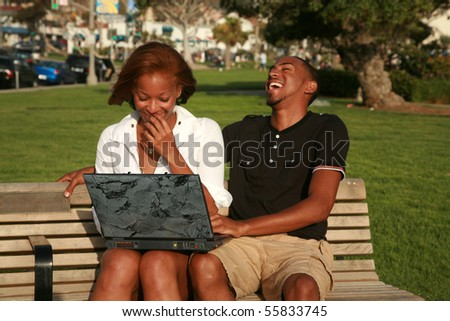 a young african american couple enjoy using a laptop computer outside