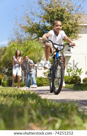 A young African American family with boy child riding his bicycle and his happy excited parents giving encouragement behind him