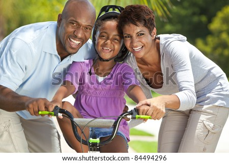 A young African American family with girl child riding her bicycle and her happy excited parents giving encouragement beside her. - stock photo