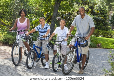 A young African American family, woman, man, father, mother & two sons  boy children riding bicycles in the summer
