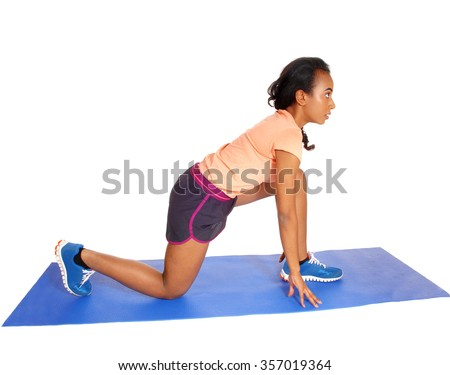 A young African American girl kneeling on a blue yoga mat, in sportswearisolated for white background. - stock photo