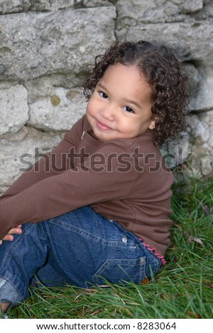 A young African American girl posing at an outdoors stone wall