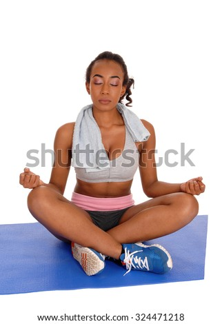 A young African American girl sitting in sports wear on a mat in a yoga position with eye's closed, isolated for white background.  - stock photo