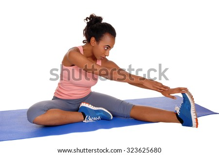 A young african american girl sitting on a yoga mat, stretching her body,for fitness, isolated for white background. - stock photo