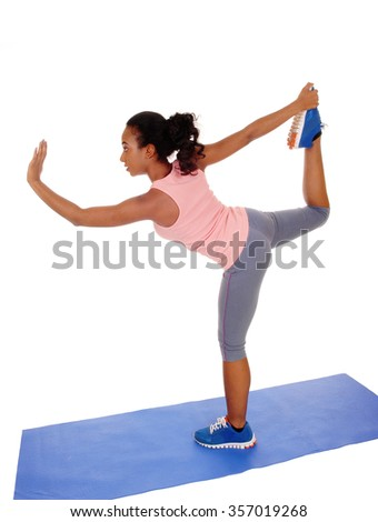A young African American girl standing on a yoga mat, doing stretching, in blue tights, isolated for white background. - stock photo