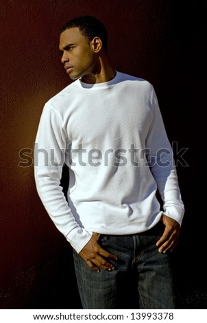 A young African American pan posing outside against a brown background.
